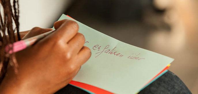 Eine Hand schreibt auf einer Moderationskarte