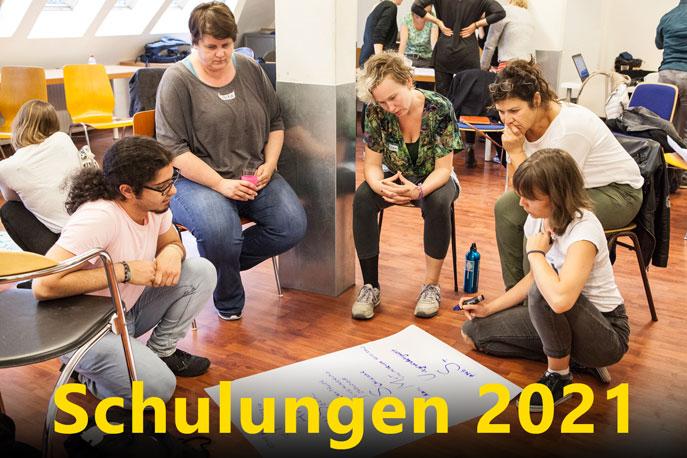 Foto von einem Workshop, fünf Leute sitzen um ein Plakat